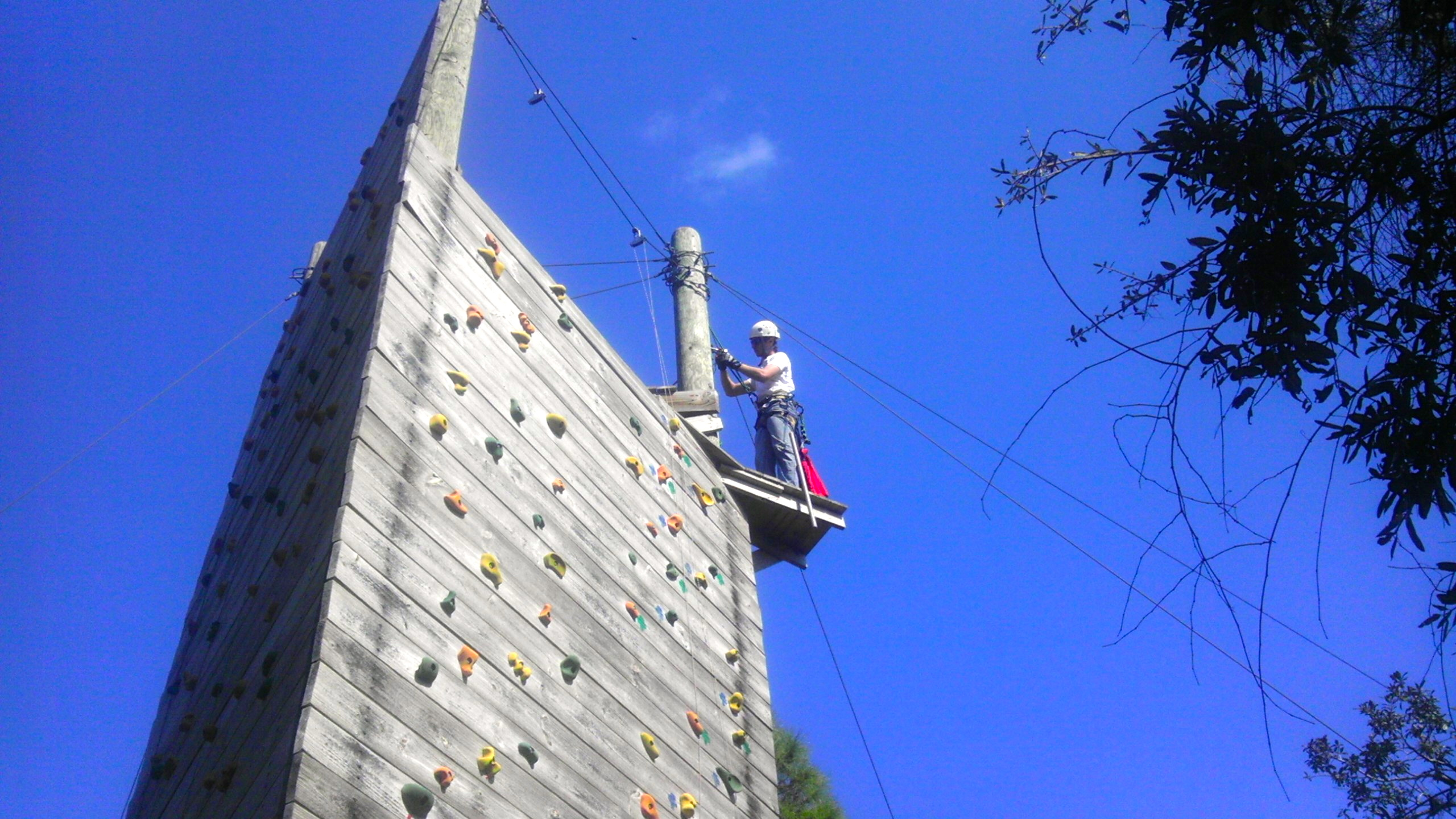 Inspector working on a Climbing Wall. Inspection practices and other Challenge Course Information can be found within our blog.